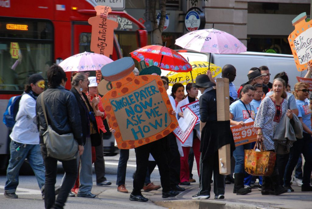 an image of a group of people protesting outdoors with lots of signs