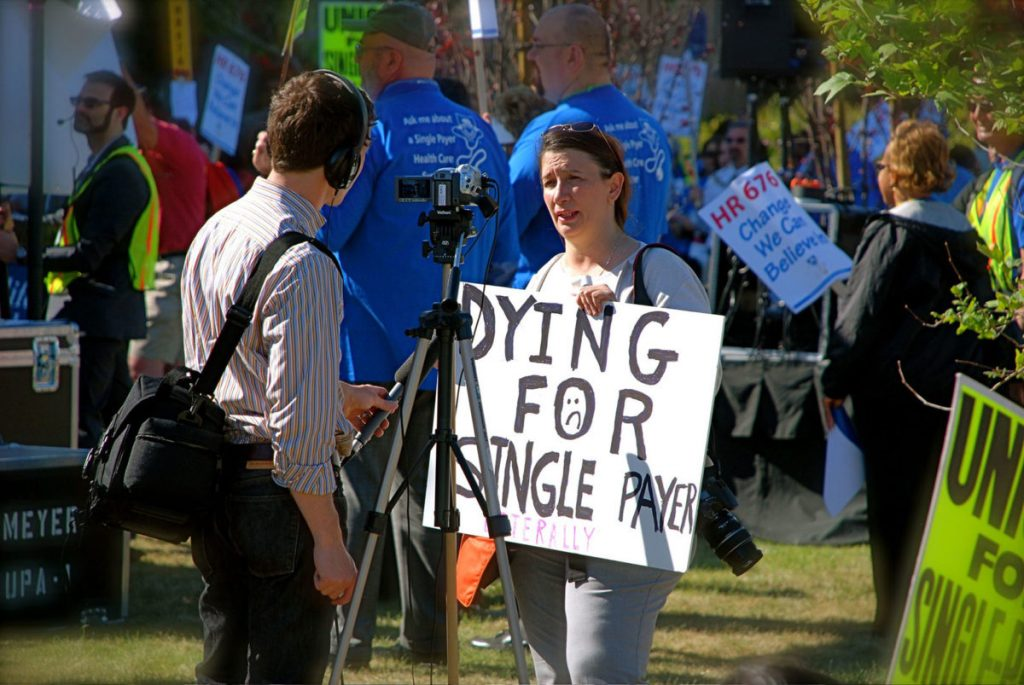 an image of a woman at single payer healthcare rally being interviewed by a reporter