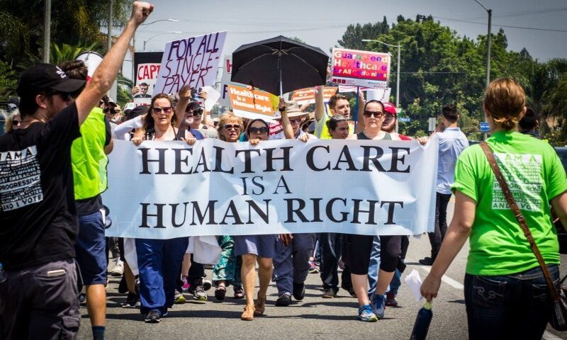 large group of people holding a health care is a human right banner