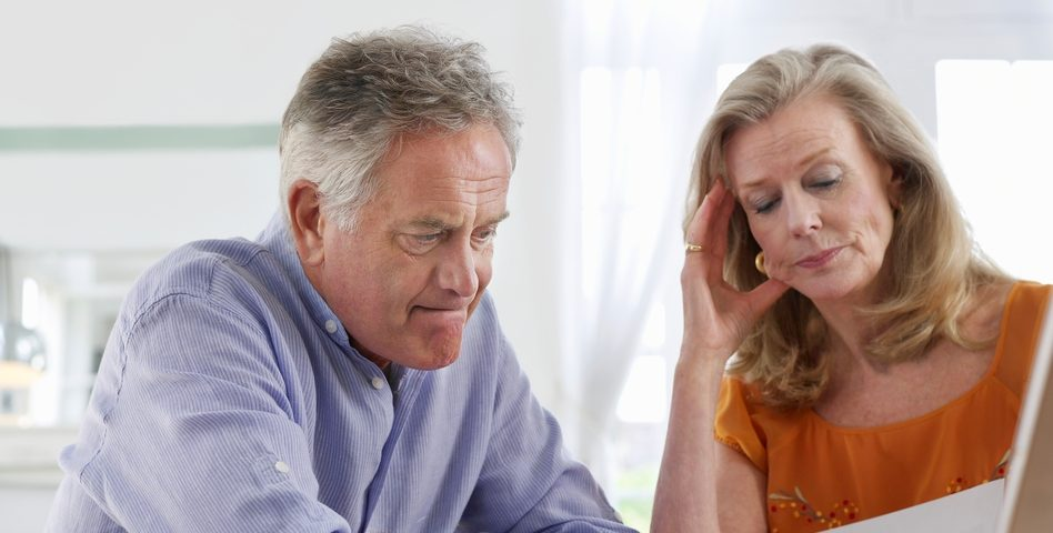 older couple looking at paperwork with frustrated look on face
